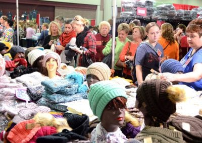 Large crowd of women shopping for wholesale hats